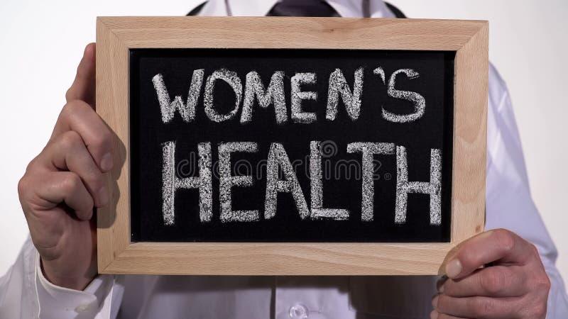 Santé de femmes écrite sur le tableau noir dans des mains de gynécologue, médecine reproductrice photographie stock