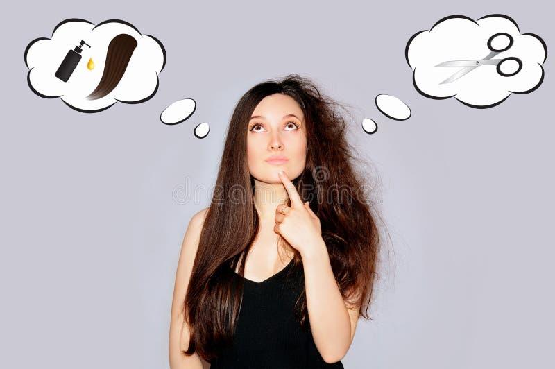 Santé et beauté Jeune femme regardant les pointes fourchues Astuces de cheveux photos stock