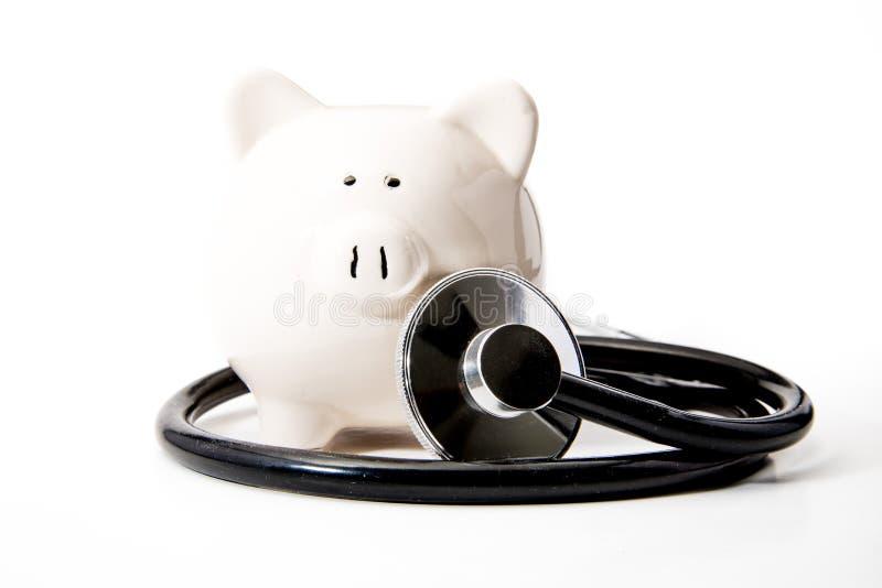 Santé financière - stéthoscope noir et tirelire photographie stock libre de droits