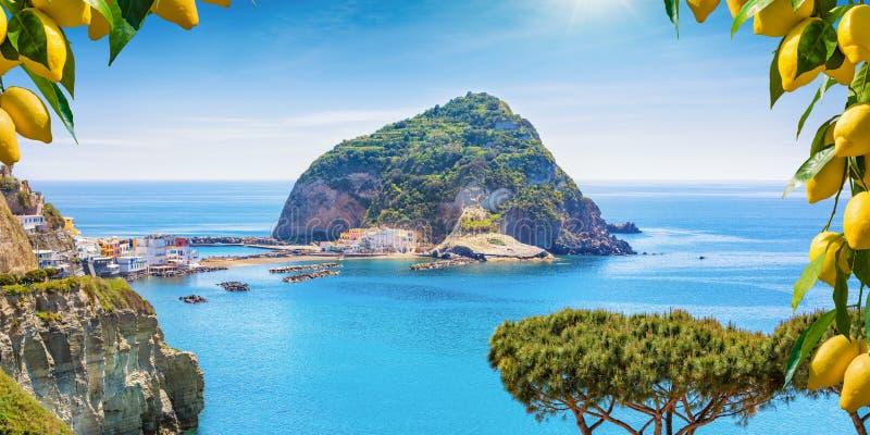 Sant`Angelo village, giant green rock in blue sea near Ischia Island, Italy. Beautiful coast of village Sant`Angelo, giant green rock in blue sea near Ischia stock photo