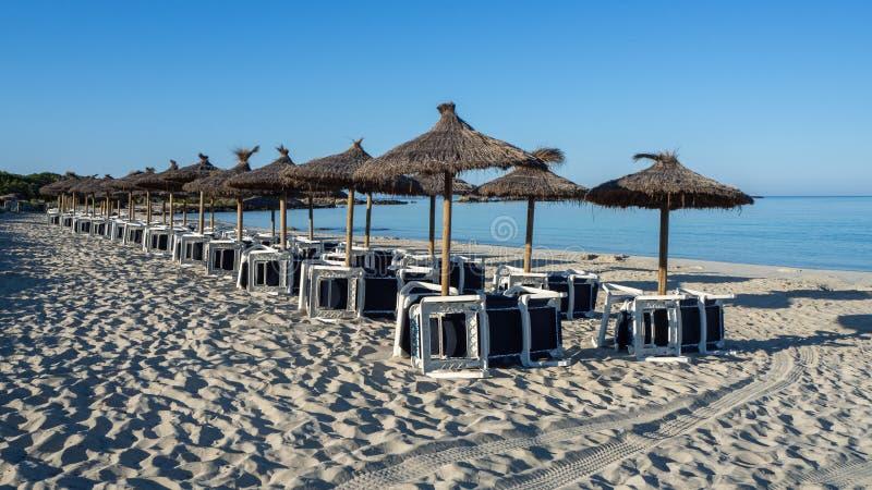 Sant Jordi de Colonia, Mallorca, España Playa con los paraguas y los sunbeds de la paja por la mañana sin la gente imagen de archivo libre de regalías