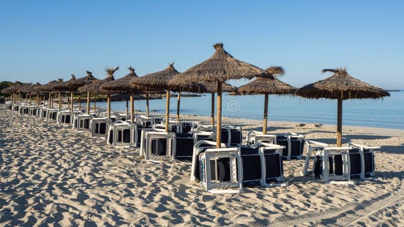 Sant Jordi de Colonia, Mallorca, España Playa con los paraguas y los sunbeds de la paja por la mañana sin la gente fotos de archivo