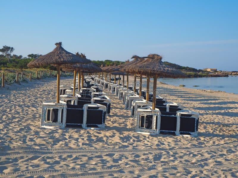 Sant Jordi de Colonia, Mallorca, Espa?a Playa con los paraguas y los sunbeds de la paja por la ma?ana sin la gente fotografía de archivo libre de regalías