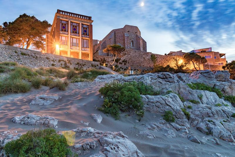 Sant Marti Empuries church from behind. Sant Marti Empuries church and rocky coast at night royalty free stock images