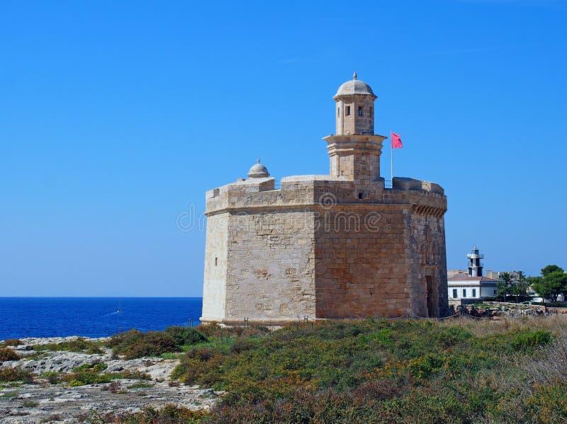 Sant Nicolau Castle en menorca del ciutadella en los acantilados con el mar azul del verano y el faro en la distancia foto de archivo libre de regalías