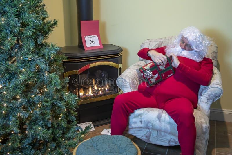 Sant que desempaqueta el regalo después de la Navidad imagenes de archivo