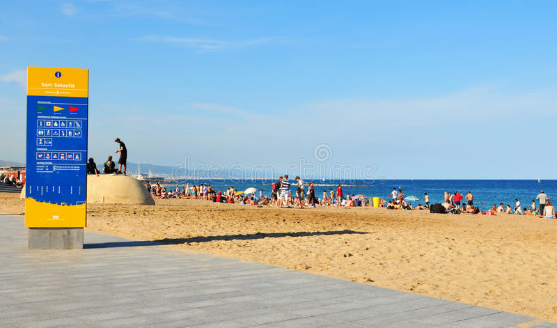 Sant Sebastia beach in Barcelona. Barcelona, Spain - 6 July, 2012: Tourist enjoying the sun on the Sant Sebastia (Saint Sebastian) beach in Barceloneta, Spain stock images
