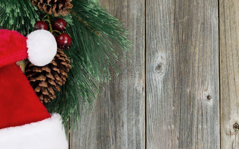 Santa ΚΑΠ με τον αειθαλή κλάδο και κώνοι στους ξύλινους πίνακες στοκ φωτογραφία με δικαίωμα ελεύθερης χρήσης