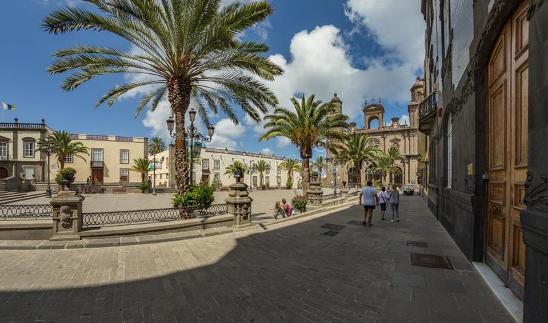 Santa Ana Cathedral and square in La Vegueta of Las Palmas de Gran Canaria with people enjoying the sunny day under the shade of. Palm trees and radiant blue royalty free stock images