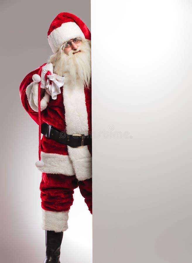 Santa avec le sac sur l'épaule présentant le conseil vide images stock