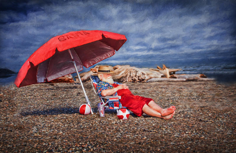 Santa on the beach. Santa Claus on vacation, sitting on a beach under a large umbrella in summer stock photography