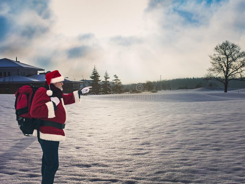 Santa with a big red backpack standing in a winter snow-covered stock photography