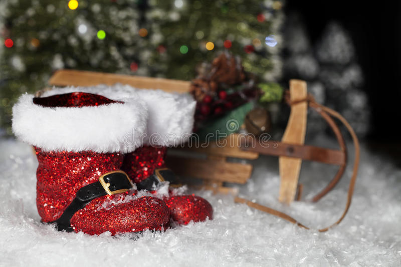 Santa Boots and Sleigh. Sparkling red Santa boots and old fashioned wood sleigh in snow with Christmas trees blurred in background stock images