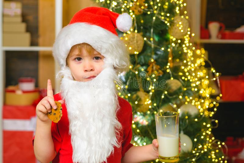 Santa boy in Santa hat. Funny child Christmas. Santa Claus - bearded funny child. Happy Santa Claus - little child boy. With glass of milk and cookie. Christmas stock image
