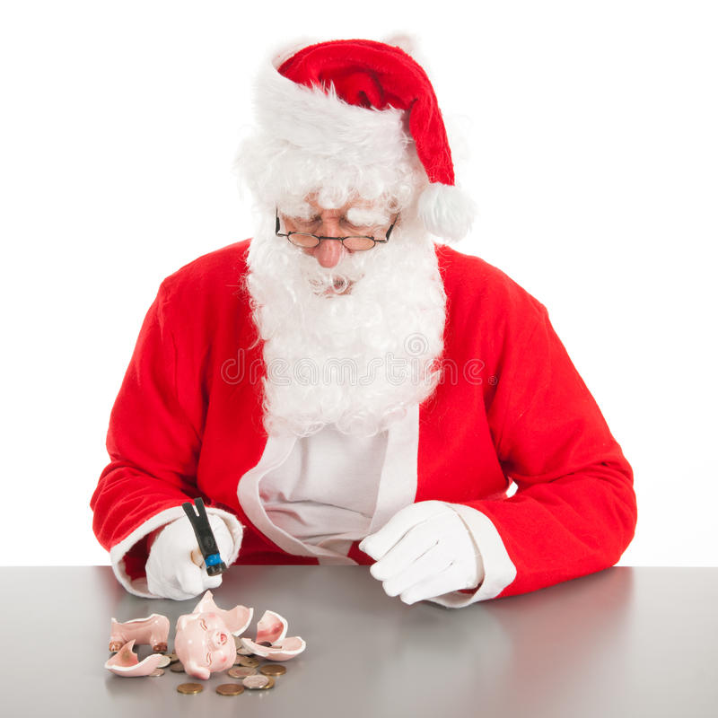 Santa breaking poor piggy bank. Santain breaking his piggy bank with only coins in it royalty free stock photography