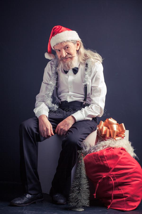 Santa cansado velha que senta-se na cadeira com saco do presente próximo fotografia de stock royalty free