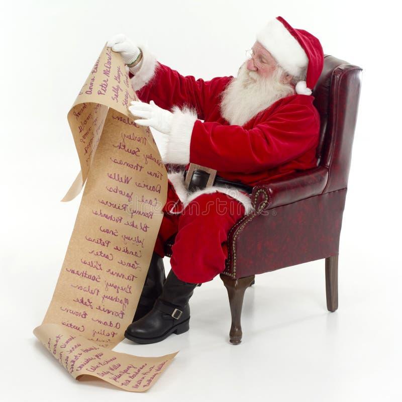 Santa che controlla la sua lista fotografia stock libera da diritti