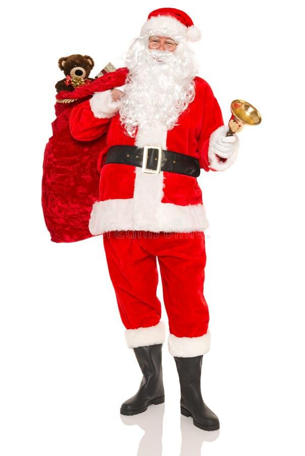 Santa che porta un sacco in pieno dei regali isolati fotografia stock