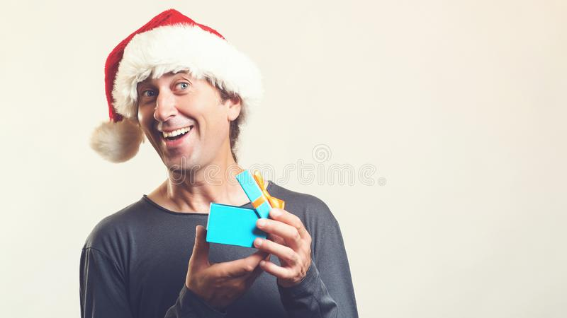 Santa christmas man opening gift box present. Amazing man in Santa hat isolated on white, with copy space. Christmas holidays. Happy man enjoying Christmas stock photography
