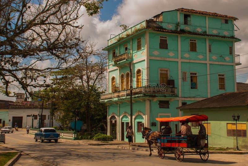 SANTA CLARA, CUBA: A rua usual na cidade Construção verde do multi-andar Carro Horse-drawn Carro do cavalo para transportar povos fotografia de stock royalty free