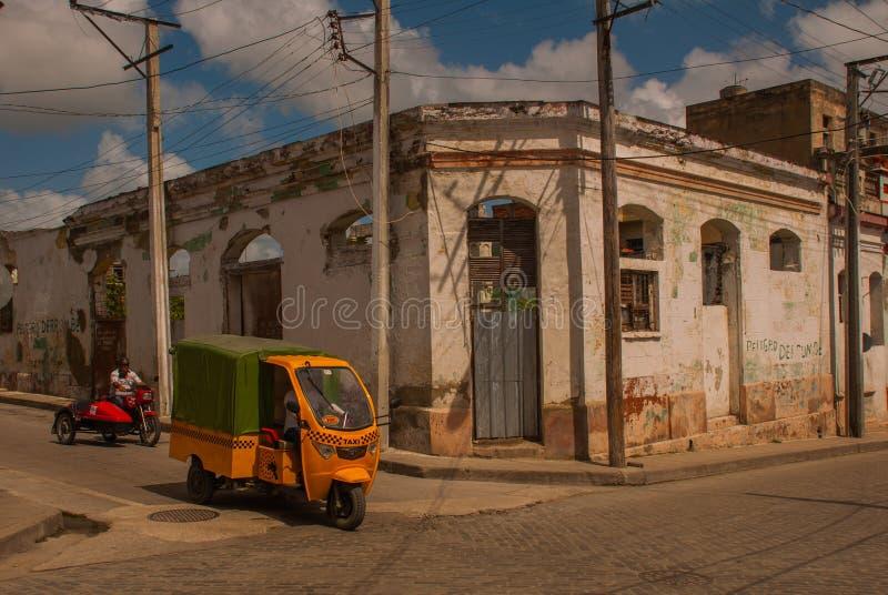 SANTA CLARA, KUBA: Motocyklu taxi jedzie na drogowej, typowej ulicie w śródmieściu stolica Kubańska prowincja, fotografia royalty free