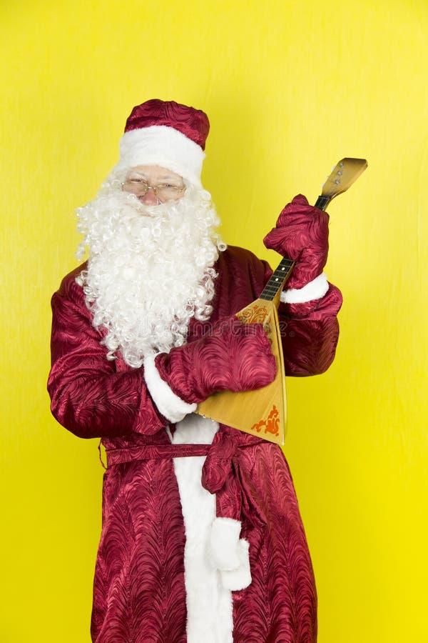 Santa Claus är förlovad i musik Santa Claus har gyckel som spelar ett musikinstrument arkivfoton