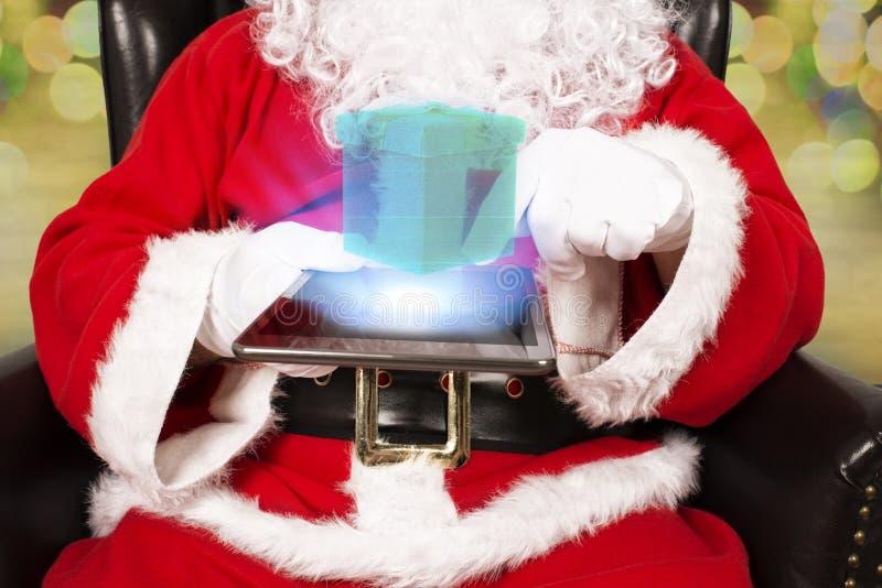 Santa Claus é guardando e de toque uma tabuleta digital foto de stock royalty free