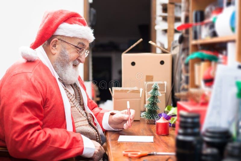 Santa Claus écrivant une lettre sur son bureau occupé photo libre de droits
