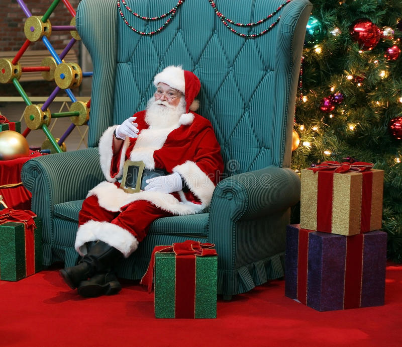 Santa Claus. Sitting in large green chair pointing finger surrounded by presents and decorations