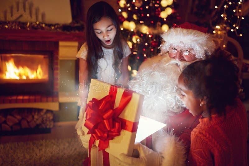 Santa Claus abre uma caixa com mágica do Natal fotos de stock royalty free