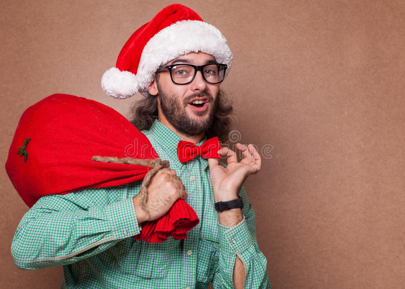 Santa Claus alla moda ha deriso la tenuta della borsa con i regali fotografie stock libere da diritti