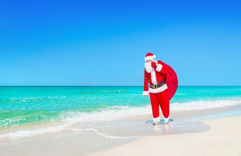Santa Claus anda com o grande saco dos presentes do Natal na praia do oceano fotos de stock