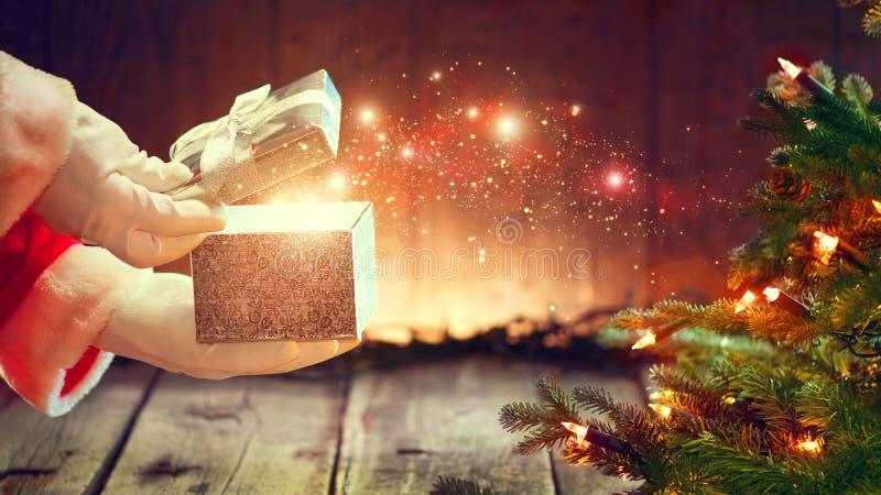 Santa Claus apre il contenitore di regalo sopra fondo di legno fotografia stock