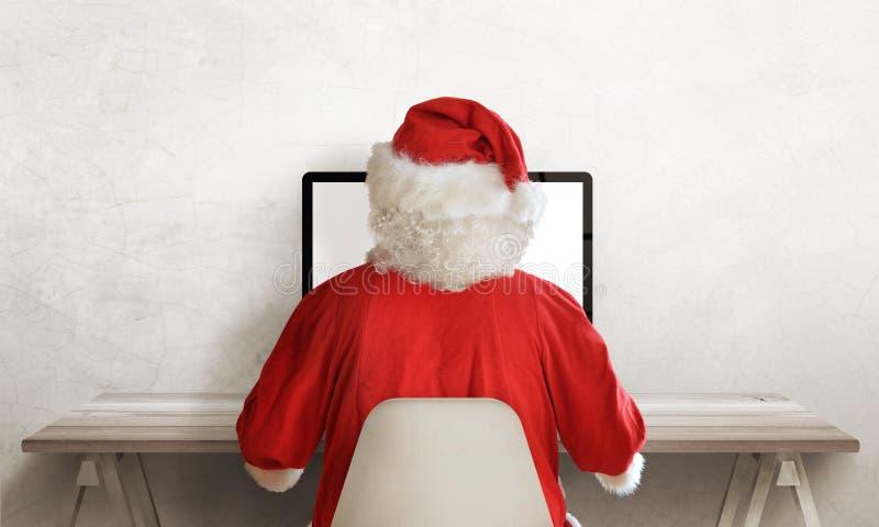 Santa Claus arbete på datoren Sikt från baksida Fritt utrymme beside från text Töm arbetsskrivbordet royaltyfri foto