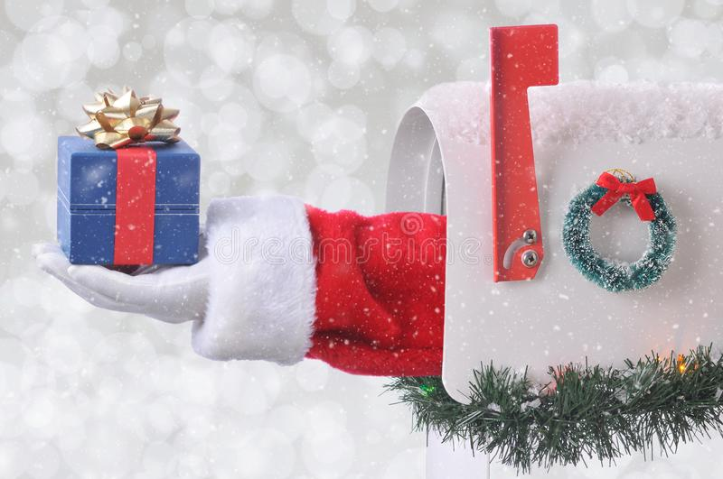 Santa Claus arm holding a small Christmas Present coming out of a mail box with silver bokeh background and snow effect.  royalty free stock photos