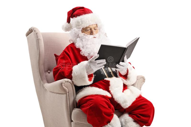 Santa Claus in an armchair and reading a book stock images