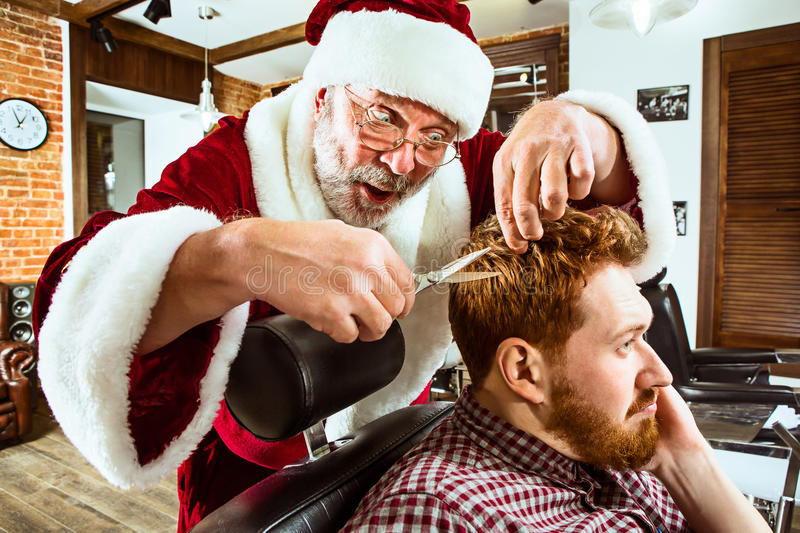Santa claus as master at barber shop stock photos