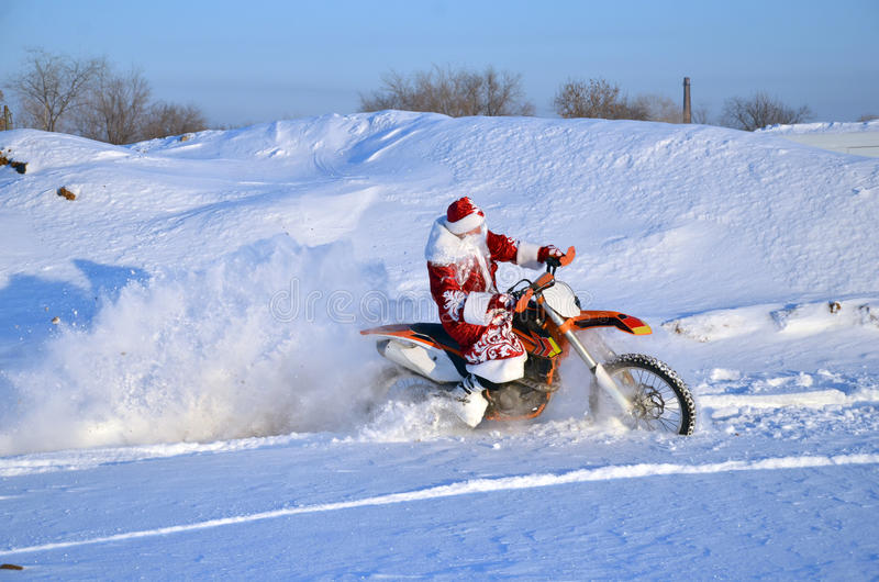 Santa Claus astride on the motocross bike. Santa Claus in a red coat and hat riding on the motocross bike on the background of a snowy field and village stock image