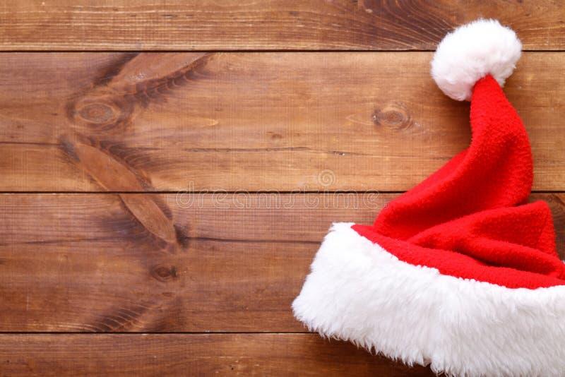 Santa Claus att gifta sig den röda hatten på brun träbakgrund som är glad julkortet med xmas-ferielocket, kopieringsutrymme, bäst royaltyfri fotografi