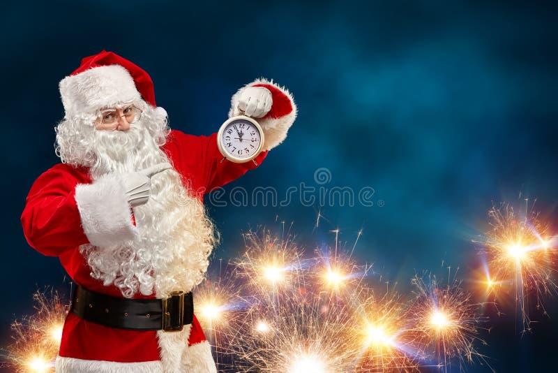 Santa Claus auf einem Schwarzhintergrund zeigt seinen Finger auf die Uhr Weihnachtsniederlassung und -glocken stockbilder