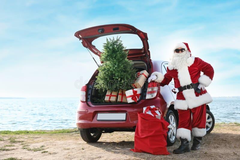 Santa Claus autêntica perto do carro vermelho com caixas de presente fotos de stock royalty free