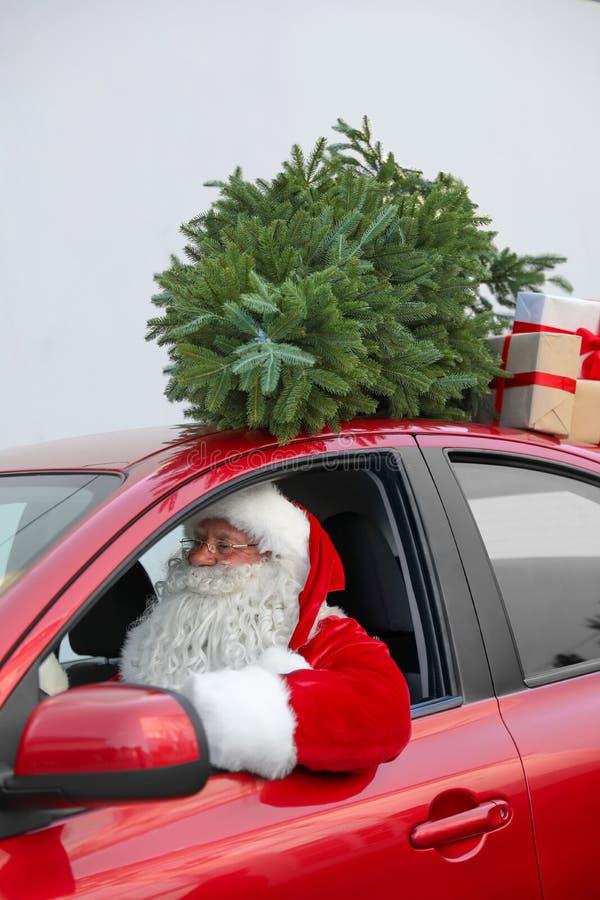 Santa Claus authentique conduisant la voiture rouge avec des boîte-cadeau photo stock