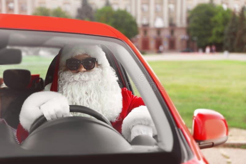 Santa Claus authentique dans des lunettes de soleil conduisant la voiture image stock