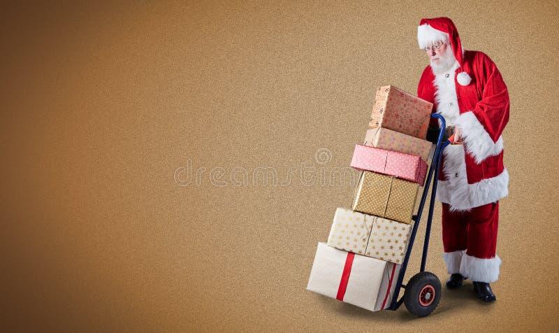 Santa Claus avec des présents empilés sur un chariot à la livraison dans un thème postal avec un espace simple de fond et de copi images stock