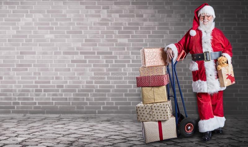 Santa Claus avec des présents empilés sur un chariot à la livraison à un thème et à un arrière-plan industriels d'entrepôt photo stock