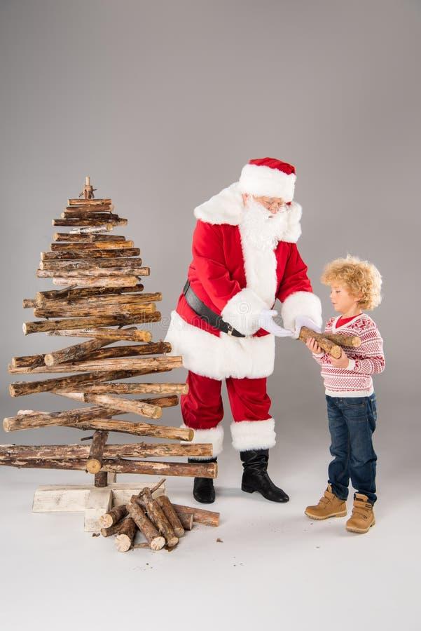Santa Claus avec l'enfant créant l'arbre de Noël photo libre de droits