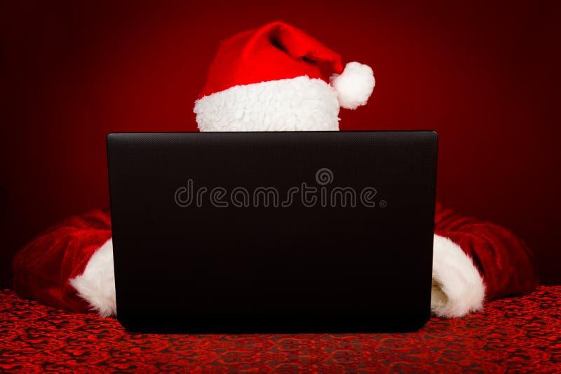 Santa Claus avec l'ordinateur portable photographie stock