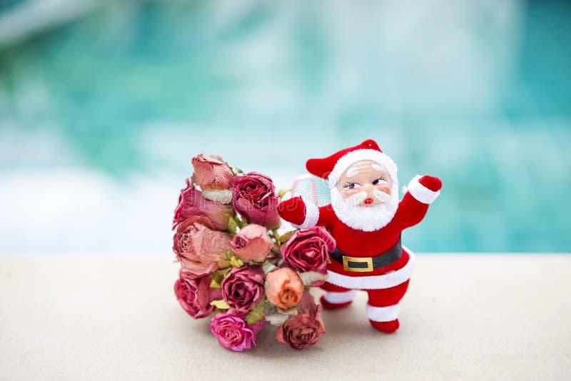 Santa Claus avec le bouquet de fleur de papier de rose au-dessus du fond brouillé de l'eau bleue photographie stock