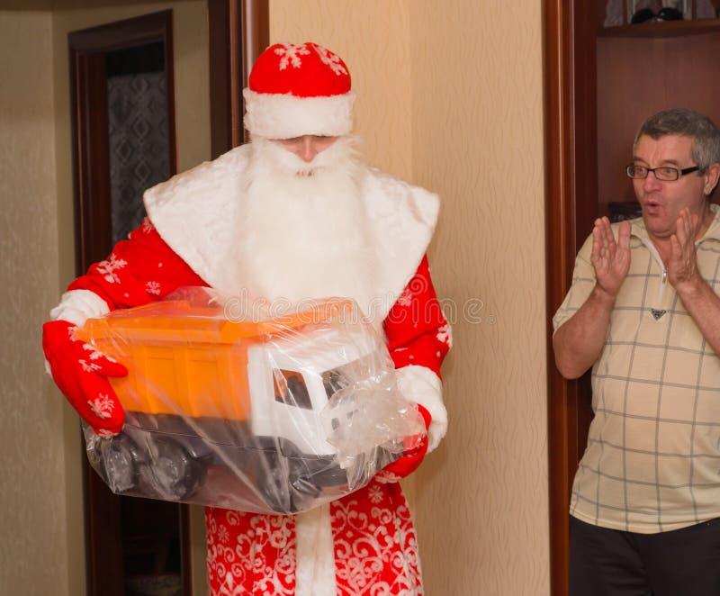 Santa Claus avec les cadeaux et le grand-père étonnés image libre de droits