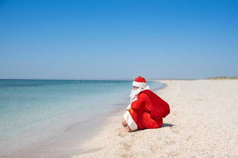 Santa Claus with a bag of gifts sitting on the sandy beach. Blue sky. Turquoise water. Copy space for your text royalty free stock photo